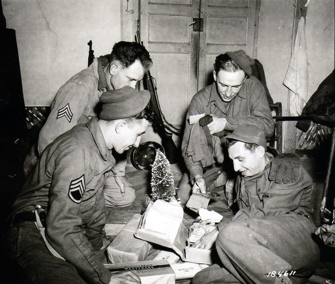 Soldiers sitting around a miniature Christmas tree and opening a Christmas package. Noted as F. A. Bn., 3rd Div. Pietramelara, Italy. December 16, 1943.