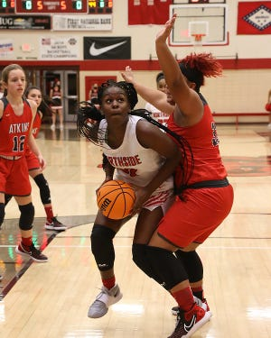 Northside's Haitiana Releford pushes into the paint past Atkins' Ashton Dillard for the shot in the first quarter, Tuesday, Dec. 15, at Kaundart-Grizzly Field House.