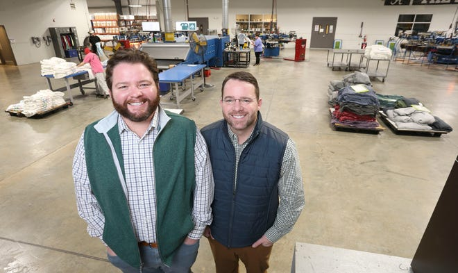 Michael Wright, left, and Nick Wright, right, of JNJ Apparel have a portrait taken inside their production facility in Northport Thursday, Dec. 16, 2020. [Staff Photo/Gary Cosby Jr.]