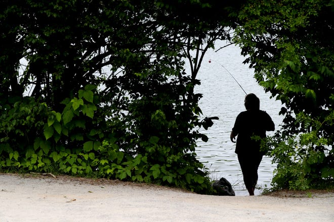 Christina Rhodes of Columbus finds a secluded fishing spot June 17 along Antrim Lake at Antrim Park.