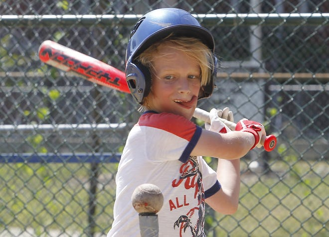 Walter Dully, 8, takes some batting practice with his father, Peter, and family friend Steve Guinan at the baseball field across from Indianola Informal K-8 School on July 21.