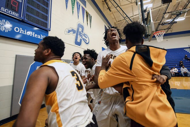 Beechcroft's Amani Lyles (center) celebrates with his teammates after defeating Eastmoor Academy in a Division II boys basketball district final March 7 at Central Crossing. Because of the COVID-19 coronavirus pandemic, the Cougars didn't get to play in the regional tournament.