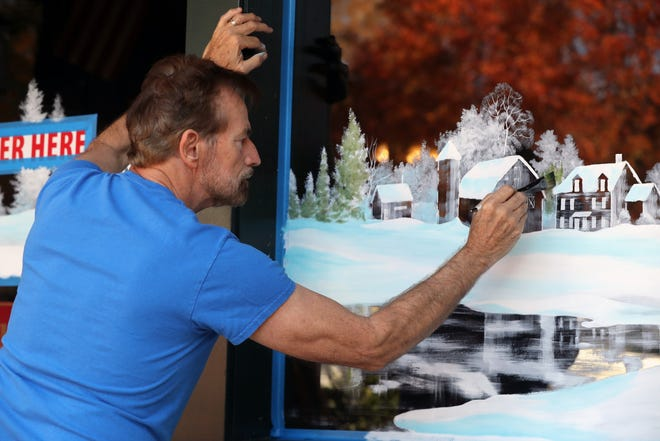Local artist Michael Dickinson paints a winter holiday scene on the windows of Schmidt's Sausage Haus and Restaurant, 240 E. Kossuth St. in German Village, on Nov. 9. For the past few years, Dickinson, 66, of Hilliard has painted the windowsat both Schmidt's Fudge Haus and Schmidt's Sausage Haus und Restaurant. He is the co-owner of the Fudge Haus with partner Tim Dick.