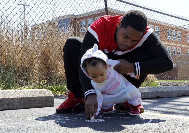 1-year-old Zenobia Harris and her father, Kareem, work on some chalk art April 6 in the parking lot of Yearling Green Apartments in Whitehall.