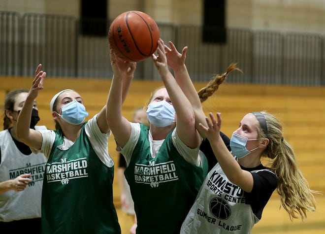 Marshfield High senior Kayla Forbes battles junior Sydney McCabe for the rebound during tryouts at the high school on Tuesday, Dec. 15, 2020.
