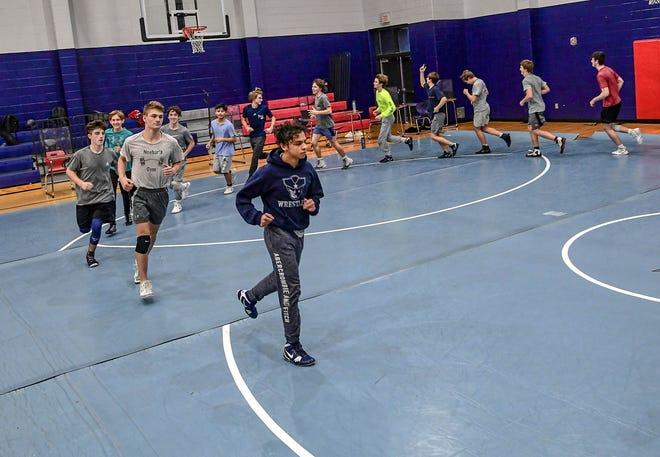 Powdersville senior wrestler Tom Ross leads a pre-match routine practice at the high school in December.