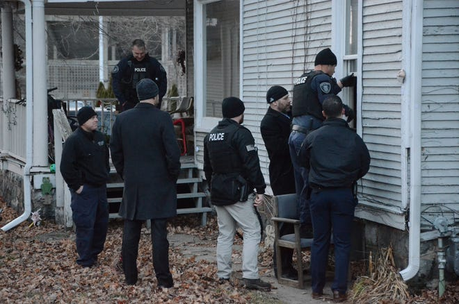 Battle Creek police open a window to enter the apartment on College Street Tuesday after obtaining a search warrant.