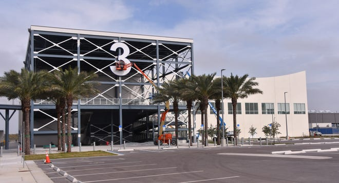 "A worker does touch-up painting work on the ""3"" outside Port Canaveral's new $155 million Cruise Terminal 3, which will be used by Carnival Cruise Line."