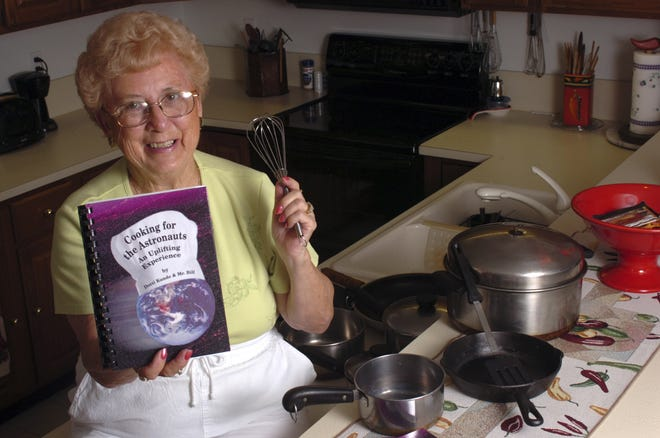 """Dotti Kunde poses at her Titusville home Friday, June 23, 2006, with her cookbook, """"Cooking for the Astronauts, An Uplifting Experience."""""""