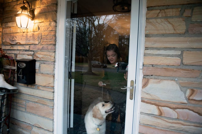 Madison Luyber, 16, in her front doorway with her dog Tuesday, Dec. 15, 2020 at her home in Moorestown, N.J.
