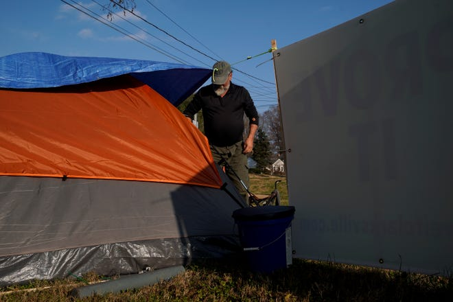 Kenny York leaves his camp chair where he chats with visitors to organize his tent and bring trash to a garbage can near the corner of Pageant Lane and Madison Street in Clarksville, Tenn., on Tuesday, Dec. 8, 2020.