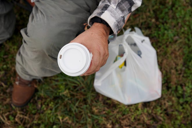Kenny York holds onto a cup of coffee brought to him by a visitor at his temporary camp site at the corner of Pageant Lane and Madison Street in Clarksville, Tenn., on Friday, Dec. 4, 2020.