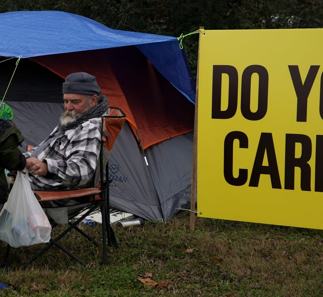 A family visits Kenny York at his campsite to drop off food for his stay in the grass patch at the corner of Pageant Lane and Madison Street in Clarksville, Tenn., on Friday, Dec. 4, 2020.