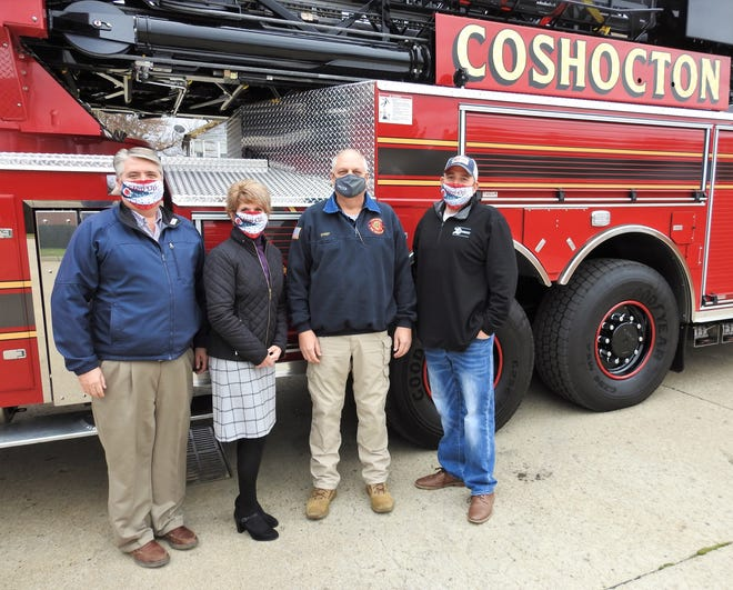 Safety Service Director Max Crown, Auditor Sherry Kirkpatrick, Chief Mike Layton and Mayor Mark Mills with the new 100-foot ladder Pierce Arrow aerial truck recently acquired by the Coshocton Fire Department for $1.3 million. The city is grateful to the public for passing an income tax levy in 2006 that has allowed for the replacement of four vehicles so far and other equipment leading to better safety and service for the community.