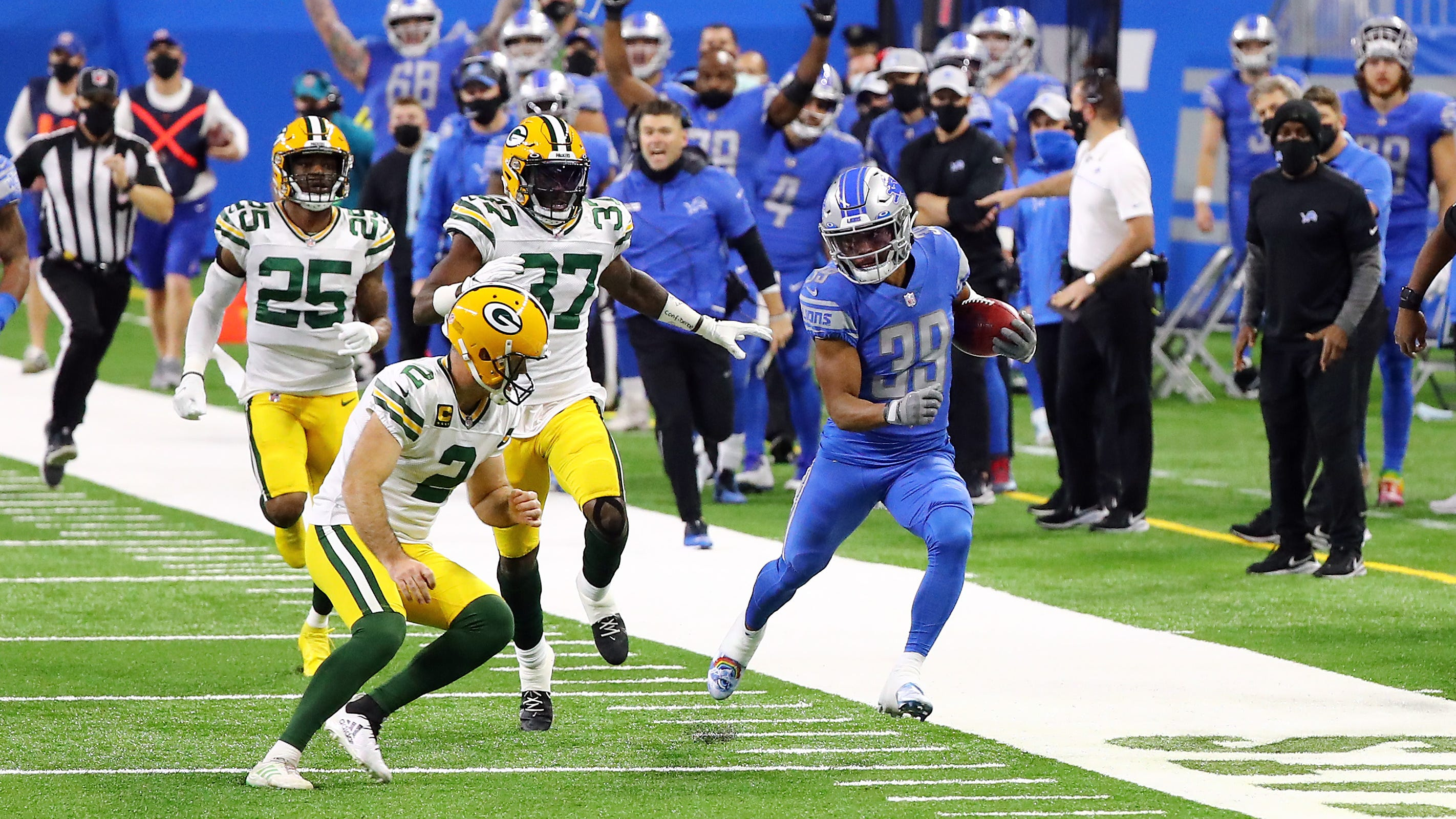 Jamal Agnew (39) of the Detroit Lions returns a kickoff before being tackled by kicker Mason Crosby (2) of the Green Bay Packers during the fourth quarter at Ford Field on Dec. 13, 2020, in Detroit, Michigan.
