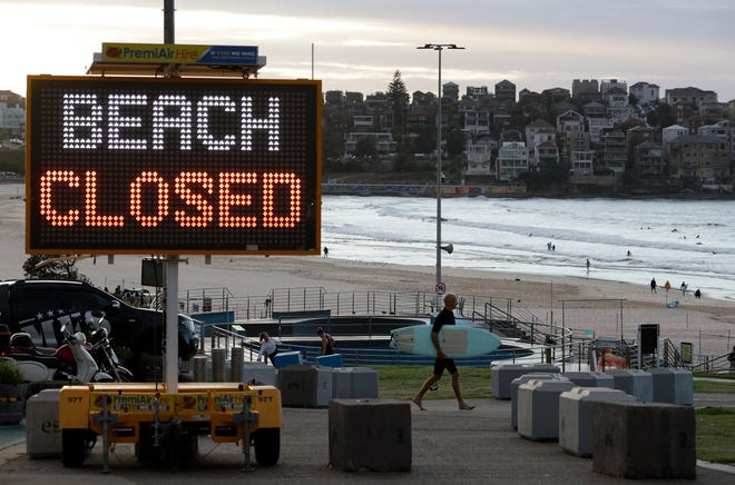 A sign indicates that Bondi Beach is closed as a surfer arrives for the 7 a.m. opening in Sydney, Tuesday, April 28, 2020, as coronavirus pandemic restrictions are eased.