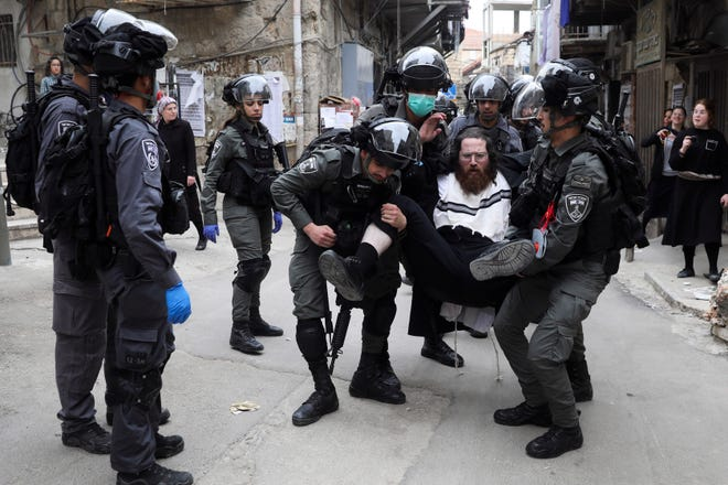 Israeli police arrest an ultra-Orthodox Jewish man during protest against government's measures to stop the spread of the coronavirus, in the Mea Shearim neighborhood of Jerusalem, on Monday, March 30, 2020.