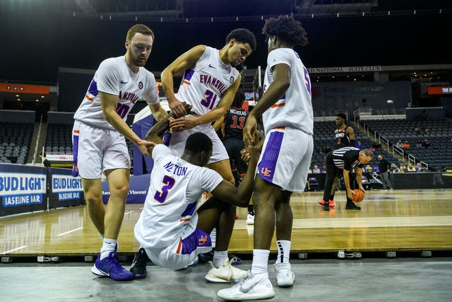 University of Evansville's Evan Kuhlman (10), Iyen Enaruna (31) and Shamar Givance (5) help their teammate Jawaun Newton (3) up after he slide off the court while attempting to recover a loose ball during the game against the Southeast Missouri State University Redhawks at Ford Center in Evansville, Ind., Tuesday, Dec. 15, 2020. The Purple Aces defeated the Redhawks 66-63 in overtime.