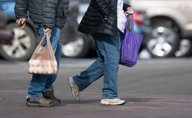 Two customers, one carrying a plastic bag and the other carrying a reusable bag, walk out of King Soopers in Fort Collins, Colo. on Sunday, Dec. 16, 2020.