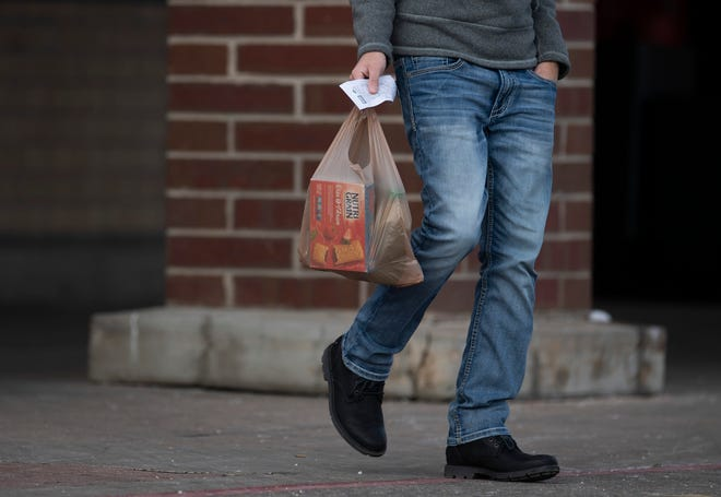 A customer walks out of King Soopers carrying a plastic bag in Fort Collins, Colo. on Sunday, Dec. 16, 2020.