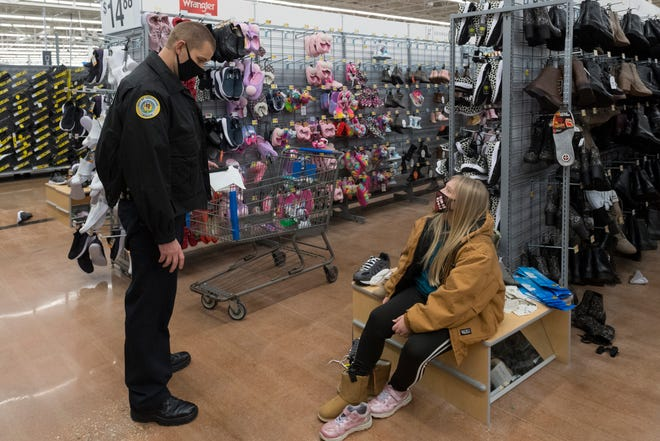 Henderson police chief Heath Cox and Kaylee Shaw, 11, shop for new shoes during the Fraternal Order of Police Lodge No. 9 annual Cops and Kids shopping event at Walmart in Henderson, Ky., Tuesday evening, Dec. 15, 2020.