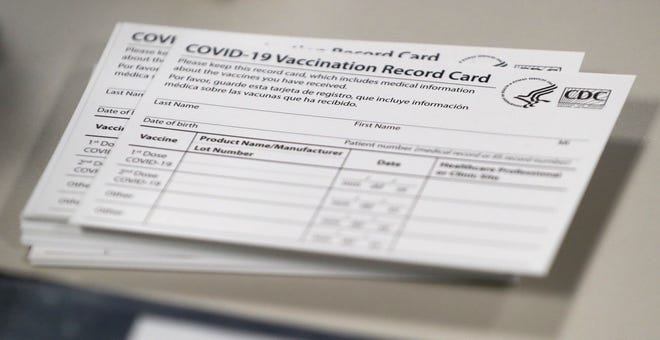 COVID-19 vaccination record cards sit on a table Wednesday, Dec. 16, 2020, at IU Health Methodist's Neuroscience Center in Indianapolis. The hospital administered the first doses of the COVID-19 vaccines to frontline medical workers.