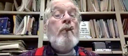 Attorney Thomas McAdam puffs a cigar during a remote probate hearing.