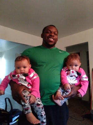Savon Hicks pictured with his twin daughters. Hicks was killed Dec. 11, 2020, in Lansing.