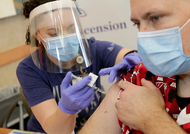 ER nurse Stephanie Fidlin administers a COVID-19 vaccine to Jim Gruenewald, an Ascension Wisconsin ICU nurse, at Ascension Southeast Wisconsin Hospital in Franklin on Dec. 16.