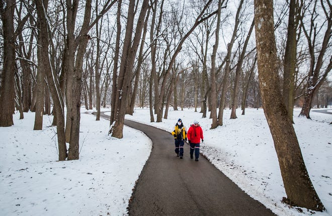 A couple walks along a paved path at Morrows Meadow after snow blanketed Delaware County during a winter storm on Dec. 16, 2020. More snow and frigid temps are expected throughout this week.