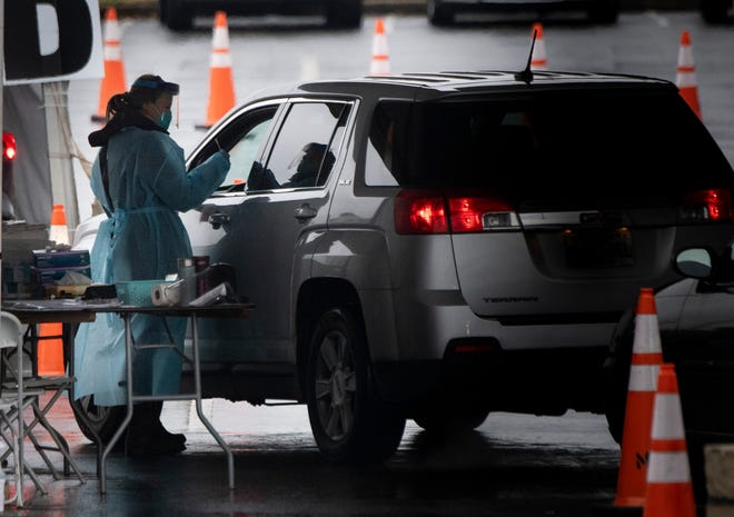 Medical personnel administer COVID-19 tests at a Community Assessment Center at Nissan Stadium Wednesday, Dec. 16, 2020 in Nashville, Tenn.
