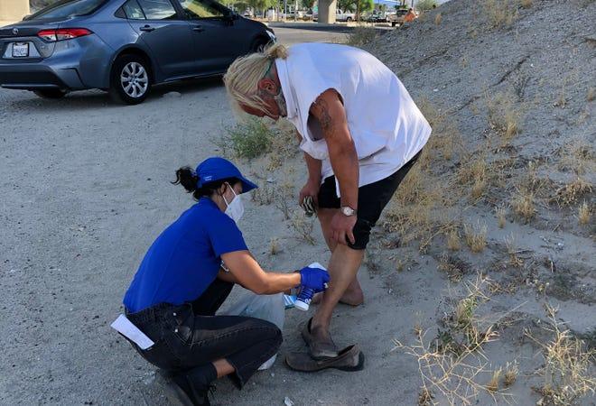 A member of the Street Medicine team provides medical assistance.