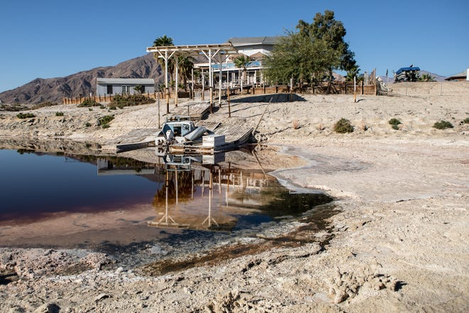 Donna and John Winters' house in Desert Shores is reflected, on Oct. 28, 2020, in a small pool in what is left of the area's canals.  The waterways were once connected to the Salton Sea and filled with water for boating and fishing.