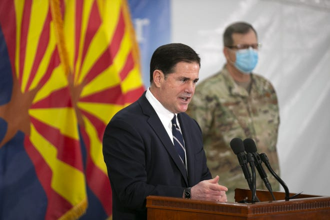 Arizona Gov. Doug Ducey speaks as Maj. Gen. Michael McGuire, director of the Arizona Department of Emergency and Military Affairs, looks on during a Dec. 16, 2020, news conference.