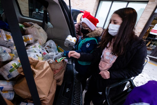 Audrey Cole, 12, helps unload a trunk full of canned goods Wednesday, Dec. 16, 2020, at the Salvation Army in Port Huron. Girl Scout Juniors Troop 76415 collected canned food around the community to donate to the Salvation Army.