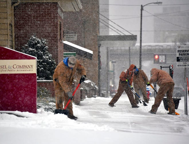 A crew from BZ Pools in Johnstown, Pa., work on shoveling the sidewalks for several of their Johnstown clients at the start of winter storm Gail on Wednesday, Dec. 16, 2020. (Todd Berkey/The Tribune-Democrat via AP)