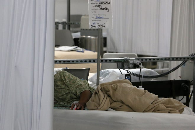 A COVID-19 patient lies in his bed in the Alternative Care Site at Renown Regional Medical Center in Reno on Dec. 11, 2020. The ACS is located on the first floor of the Mill St. parking garage.