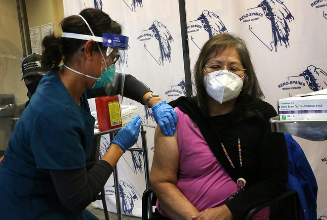 Community Health Supervisor Cordelia Abel-Johnson, right, receives one of the first COVID-19 Pfizer vaccination in the state of Nevada at the Reno-Sparks Tribal Health Center in Reno on Dec. 16, 2020. The vaccination is seen being administered by Registered Nurse Veronica Crawford.