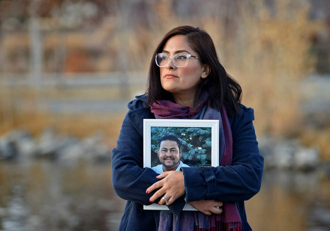 Brenda Bravo Torres stands holding a photograph of her husband Miguel Angel Lopez Villal Pinzon who died of COVID-19 in August. The Latino community had been hit  hard by COVID-19.
