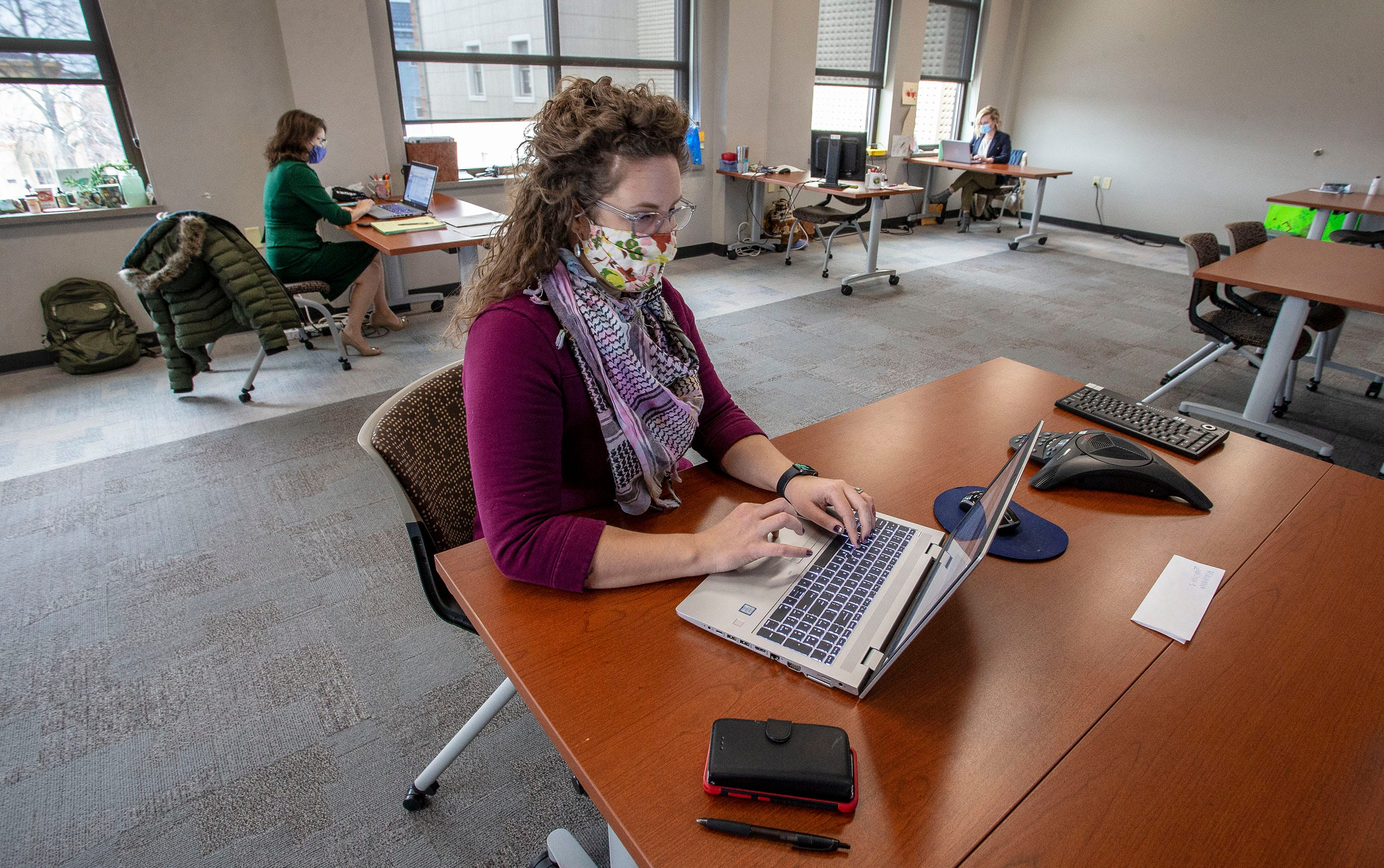 Sheboygan County Clinical Services Supervisor Amanda Strojinc, center, works on correspondence while Health Officer Starrlene Grossman, left, and Lead Health Strategist Libby Jacobs, right, work socially distanced from each other in the main conference room at Sheboygan County Health and Human Services on Wednesday, Dec. 16.