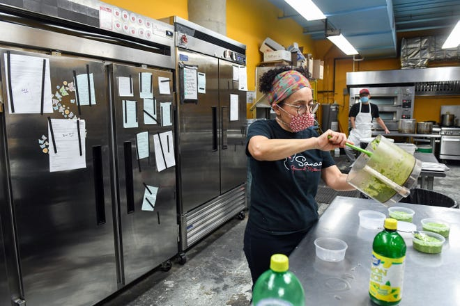 Sanaa Abourezk puts pesto into to-go containers in front of a fridge full of orders held on by magnets on Wednesday, December 16, at Sanaa's 8th Street Gourmet in Sioux Falls.