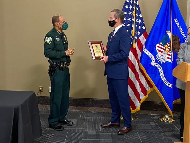 U.S. Attorney Larry Keefe (right) recognizes Leon County Sheriff Walt McNeil for his work to fight violent crime and contributions to the Justice Department's Project Safe Neighborhoods program. McNeil was honored Wednesday, Dec. 16, at the Leon County Courthouse Rotunda.