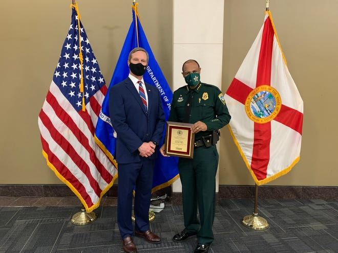 U.S. Attorney Larry Keefe (left) recognizes Leon County Sheriff Walt McNeil for his work to fight violent crime and contributions to the Justice Department's Project Safe Neighborhoods program. McNeil was honored Wednesday, Dec. 16, at the Leon County Courthouse Rotunda.
