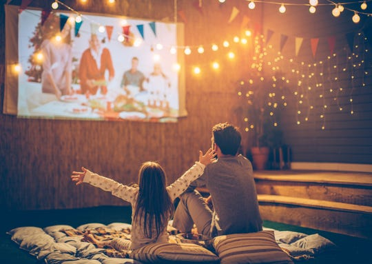A father and daughter watching a movie in the backyard.