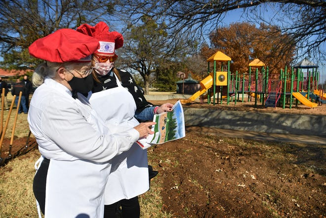 University Kiwanis Club President Mary Rhoads, left, and board member Deana Albert look over an artist's rendering of a new inclusive playground geared toward children two to five years of age that will be constructed in early 2021 at Kiwanis Park.