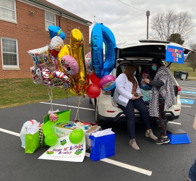 """Brinley, somewhat overwhelmed by her birthday celebration, sits in the back of her family's SUV with her cousins Kayla Luzadder and Andrea Horn. Two decades separate Brinley from her """"cuzzies,"""" but the pair remain very close to Brinley."""