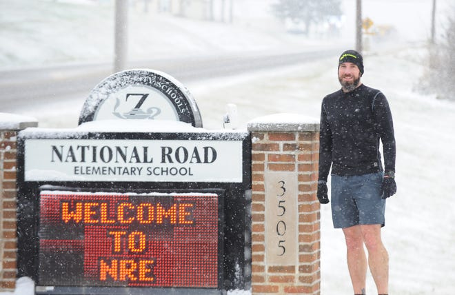 Michael Schreiber poses by the National Road Elementary sign and is the school's physical education teacher. He recently walked 619,643 steps to be named the Ohio High School Athletic Association's East District Winner for Health Action Council Step it up. His efforts led to Zanesville City Schools being awarded $2,000 to build Sensory Paths for special education students.