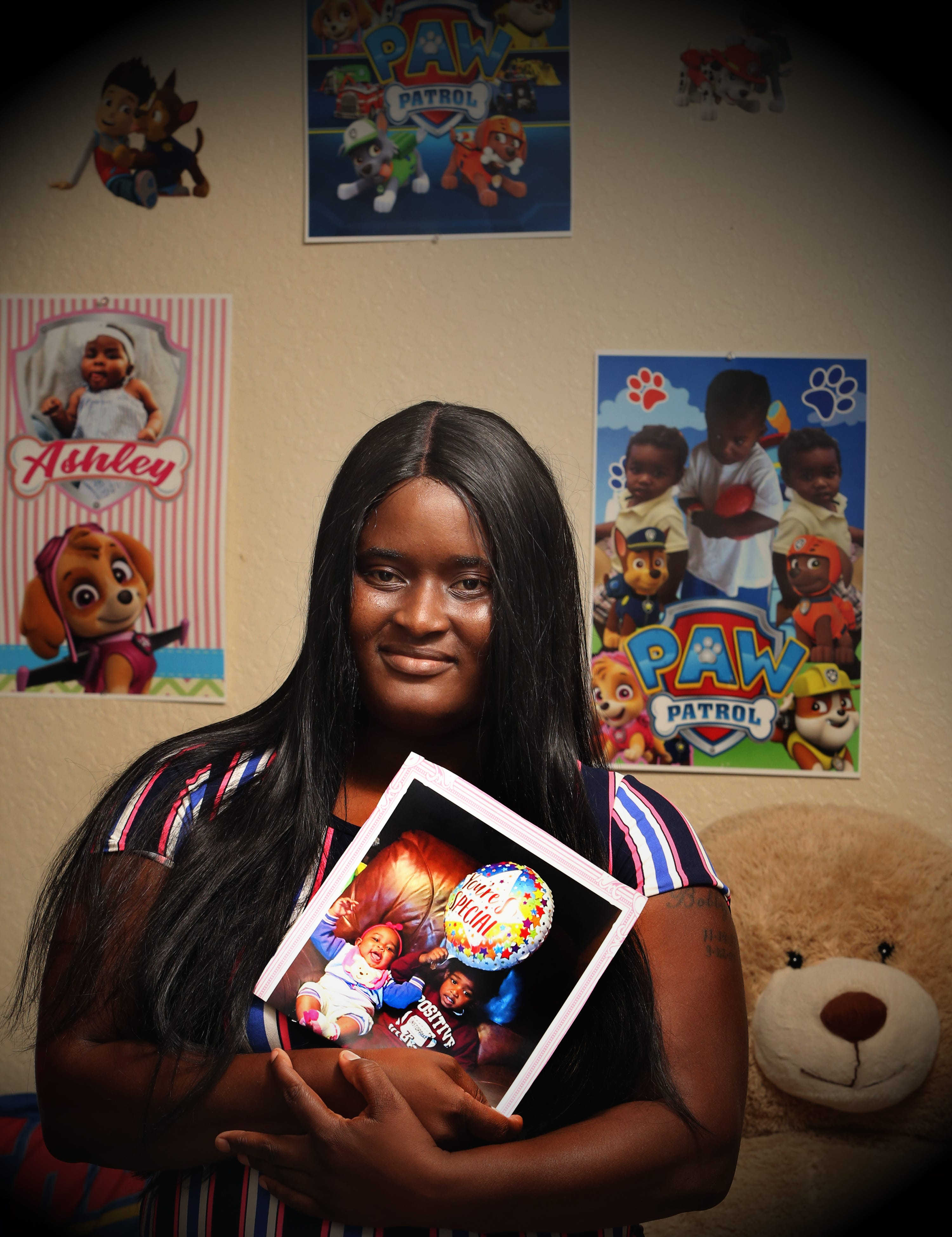 Latoya Bowles holds a photo of her children in their Riviera Beach home on Nov. 1. A judge returned her daughter and son, now 1 and 3, two weeks later.