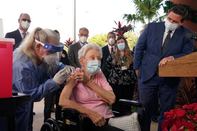 Florida Gov. Ron DeSantis watches nurse Christine Philips administer the Pfizer-BioNTech vaccine for COVID-19 to Vera Leip, 88, a resident of John Knox Village on Dec. 16 in Pompano Beach, Fla. Nursing home residents and health care workers are the first in the state to receive the vaccine.