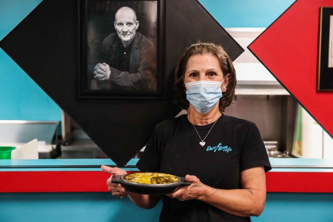 Peggy Zamarripa poses next to a photo of Dart Bowl Cafe founder Butch Martinets as she holds her famous enchiladas.
